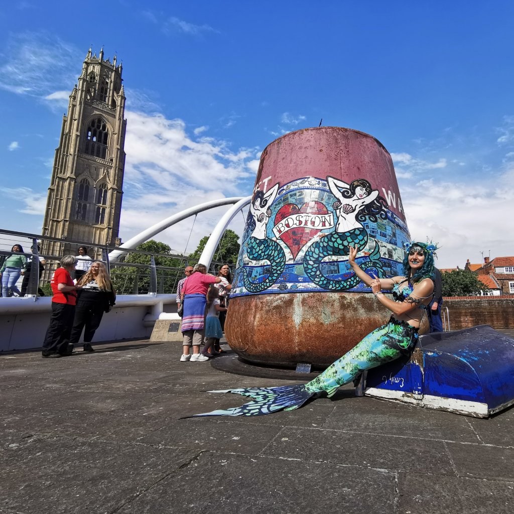 A mermaid sits next to one of the Boston Buoys designed by Carrie Reichardt