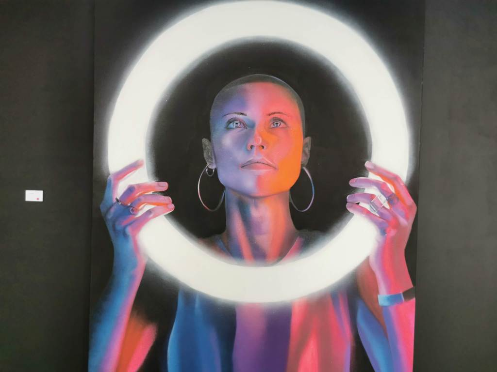 A woman holds a glowing circle, a painting by David Speed at his Light of Life exhibition