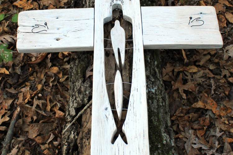 """One of the """"In Christ"""" sculptures set on an old oak log."""