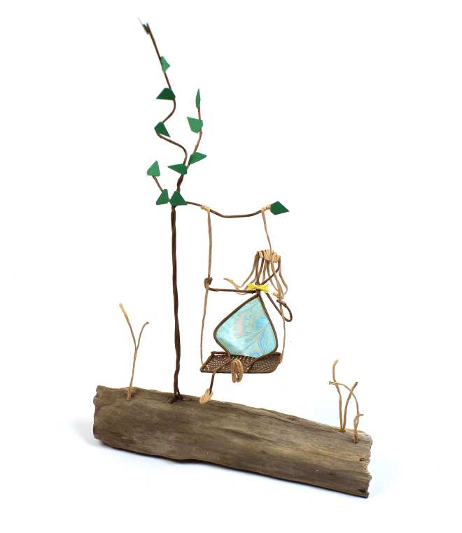 Image of Girl on a Tree Swing, a sculpture in wire and cut paper on driftwood.
