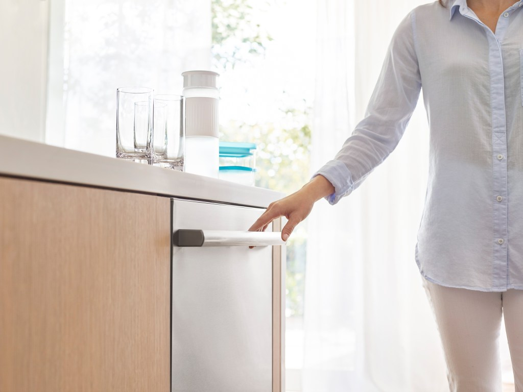 lady holding handle of Bosch dishwasher