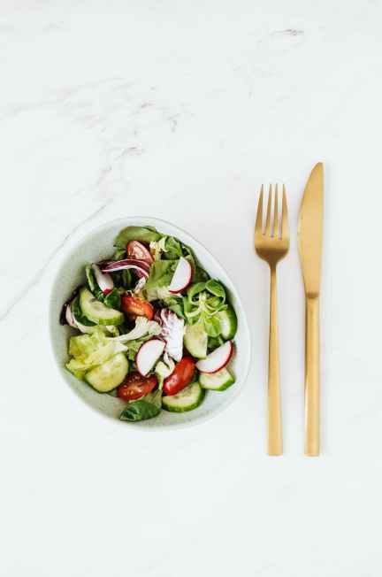 delicious vegetable salad and golden fork and knife on table