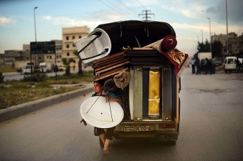 Aleppo, Syria: a boy holds a satellite dish as he travels on the back of a truck