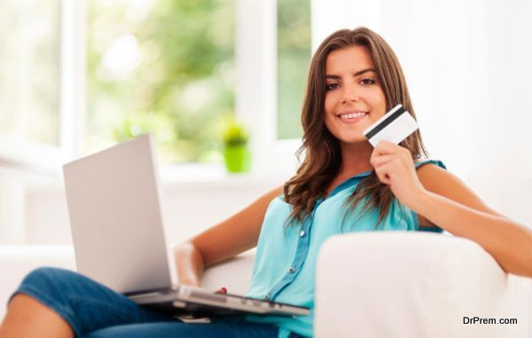 Smiling woman using laptop and holding credit card