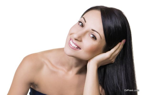 Portrait of a beautiful smiling woman with arm in her hair
