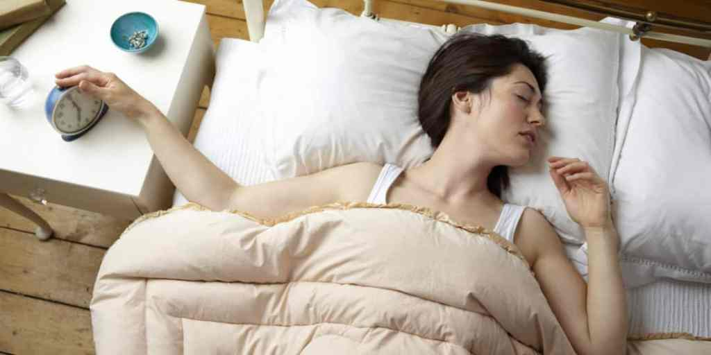 Woman in bed switching alarm off.