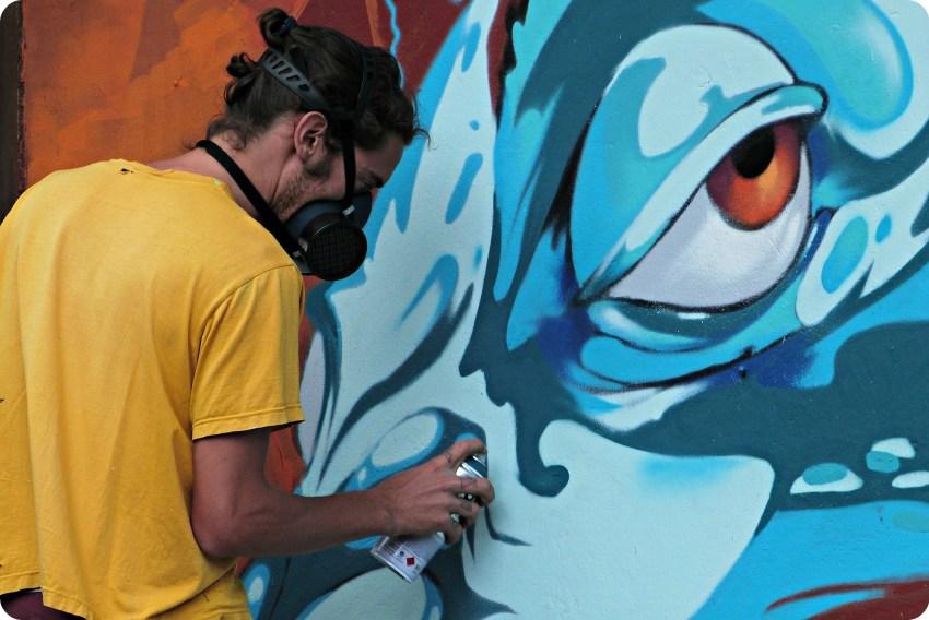 Zoom sur le graffeur en train de peindre sur un mur d'un restaurant de Bogotá