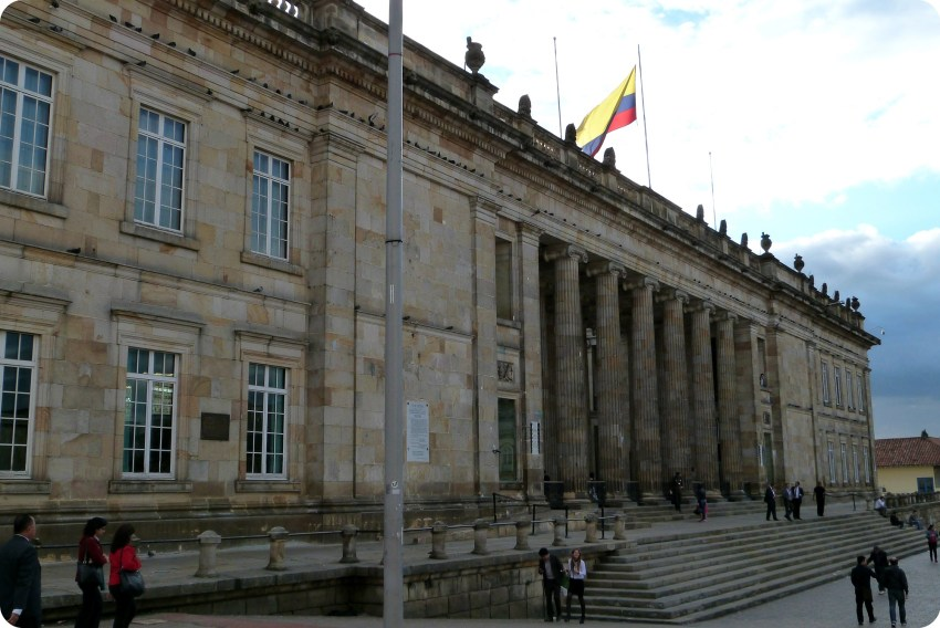 Edificio con columnas con la bandera de Colombia en la plaza Bolívar de Bogotá