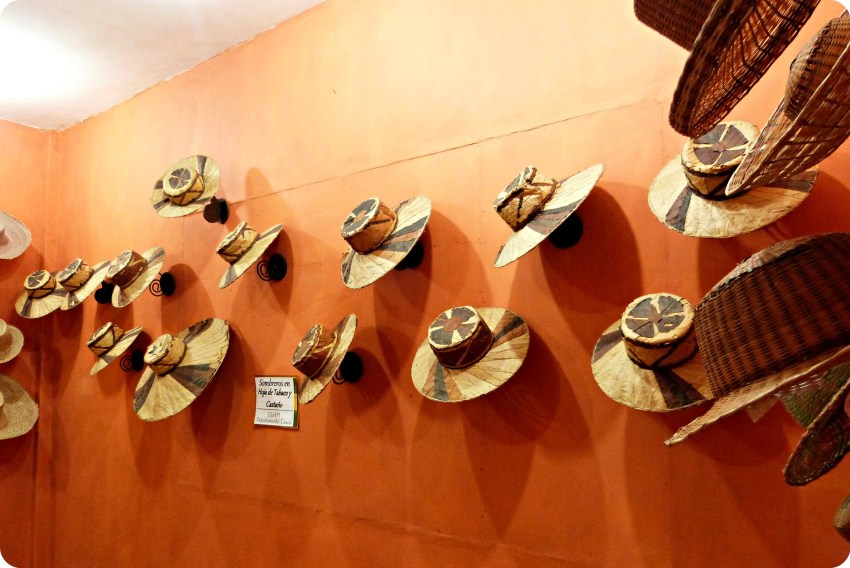 Sombreros presentandos en una pared naranja, en el museo nacional del sombrero en la casa de la cultura en Aguadas