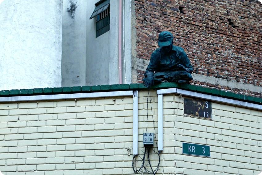 Sculpture d'un homme en haut d'un bâtiment tenant les fils d'un boîtier électrique dans le quartier de la Candelaria à Bogotá