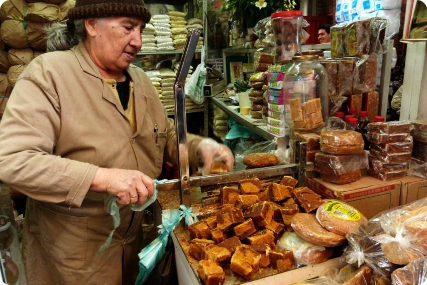 Mujer mayor cortando la panela en el mercado de Bogotá