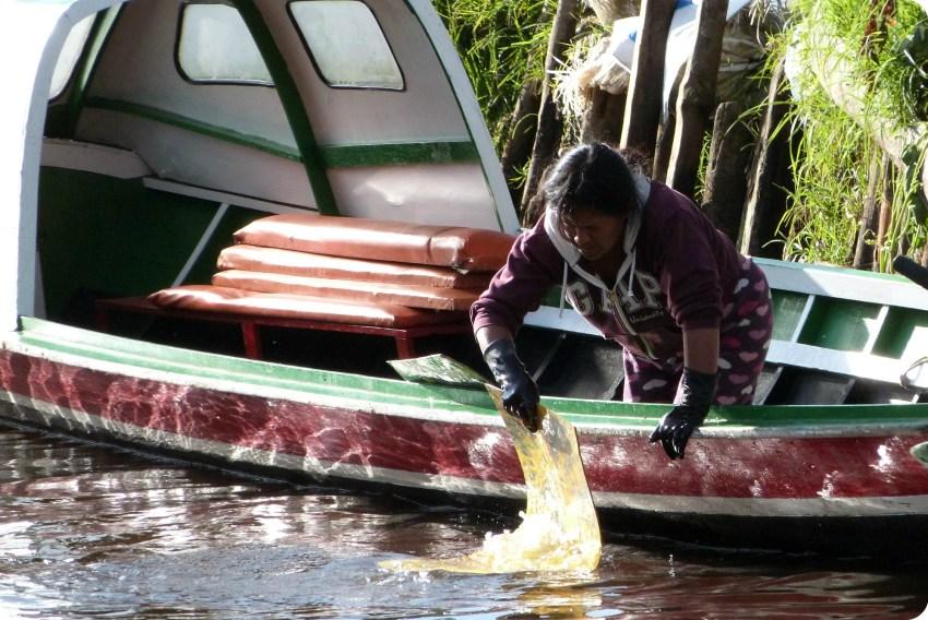 mujer lavando su tapete en el río en la laguna de la Cocha de Pasto
