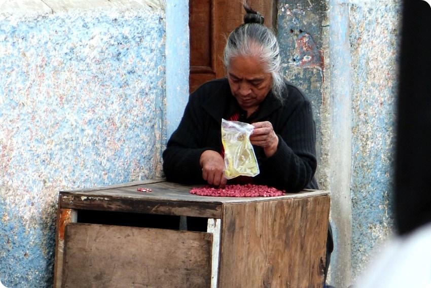 mujer seleccionando maní en una calle de Pasto