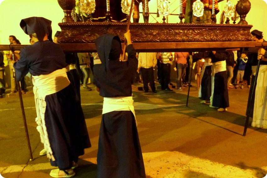moquero recuperando la cera de las velas durante el desfile del martes santo durante el desfile de la Semana Santa de Popayán