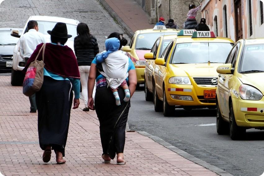 femmes équatoriennes sur un trottoir de Quito dont l'une portant un bébé dans le dos