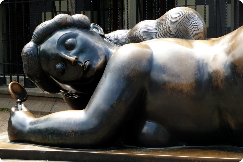 escultura de una mujer extendida con un espejo en la mano en la plaza Botero de Medellín