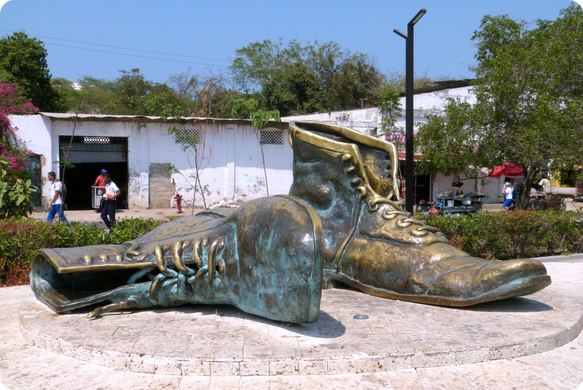 Monumento en bronce de 2 gigantes zapatos cuyo uno se echó hacia al lado cerca del castillo San Felipe de Barajas en Cartagena