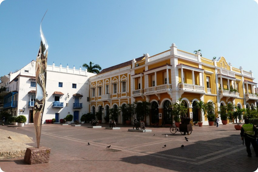 edificio amarillo y plaza con esculturas en el centro de la ciudad de Cartagena