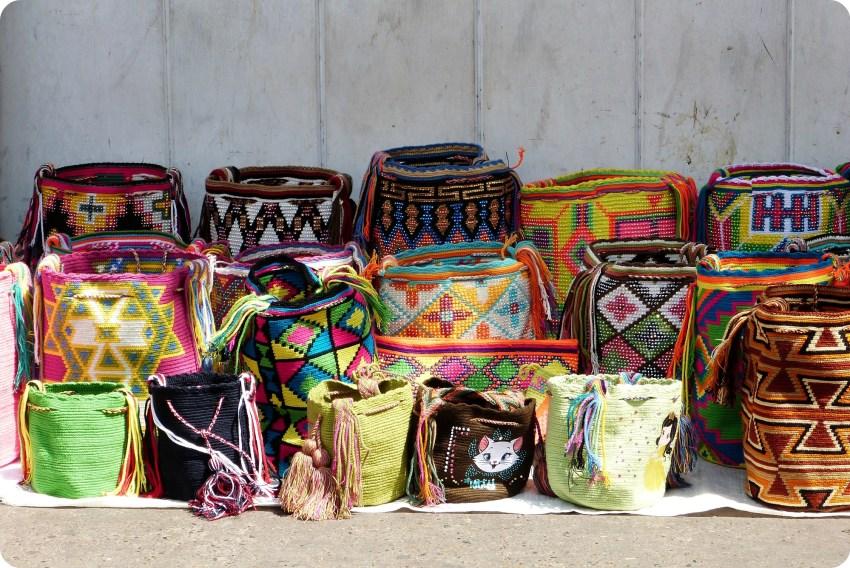 Mochilas de todos los colores fabricados por la población Wayuu expuestas a lo largo de un edificio del centro de Cartagena