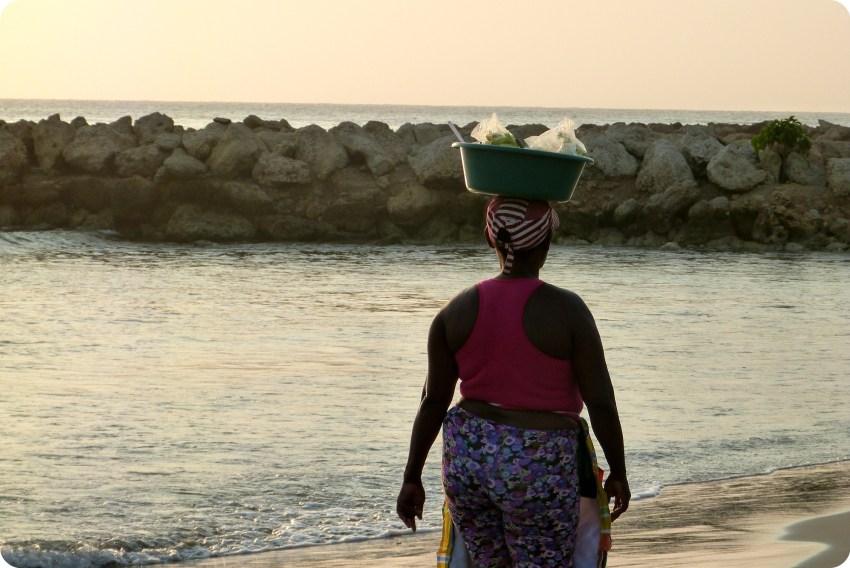 une femme transporte sur sa tête la nourriture qu'elle vend aux vacanciers sur une plage de Carthagène