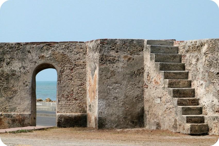 """escalera hacia las murallas de la ciudad de Cartagena y vista al mar Caribe a través de una """"puerta"""" tallada en la piedra"""