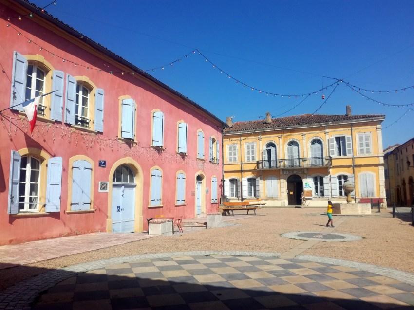 place du village Carla-Bayle façades rose et jaune petits garçons jouent au foot voyage vélo