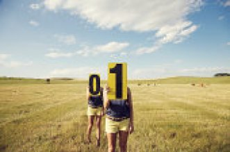Two women standing in a summer prairie field