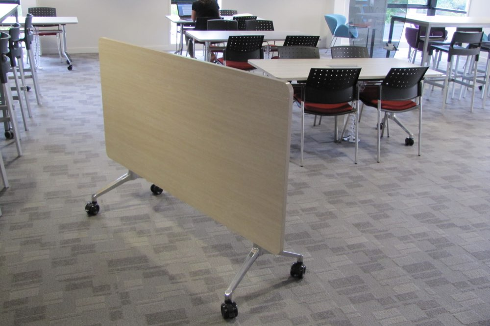 T1 RECTANGULAR Table mounted on UR Tilt Base for compact storage and mobility.