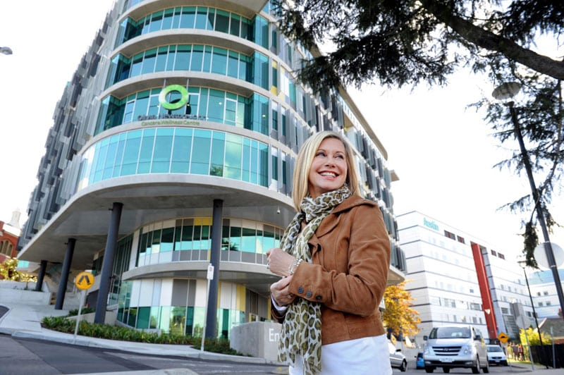 Olivia in front of the Olivia Newton-John Cancer Wellness and Research Centre
