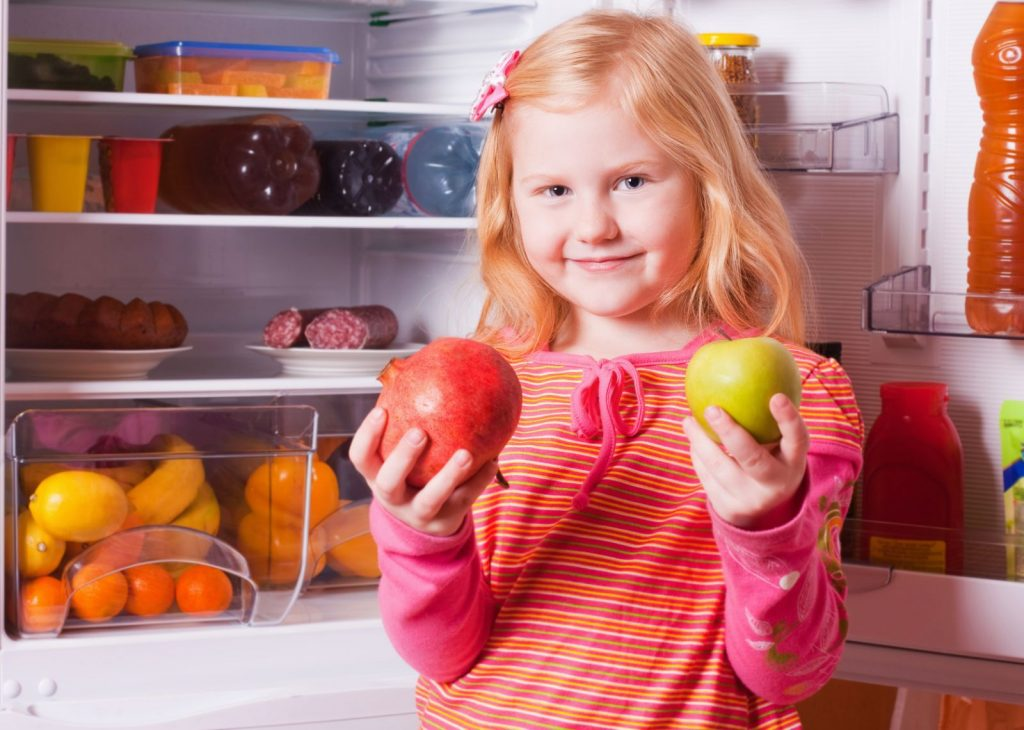 Gadis dengan sebiji epal dan delima di tepi peti sejuk terbuka