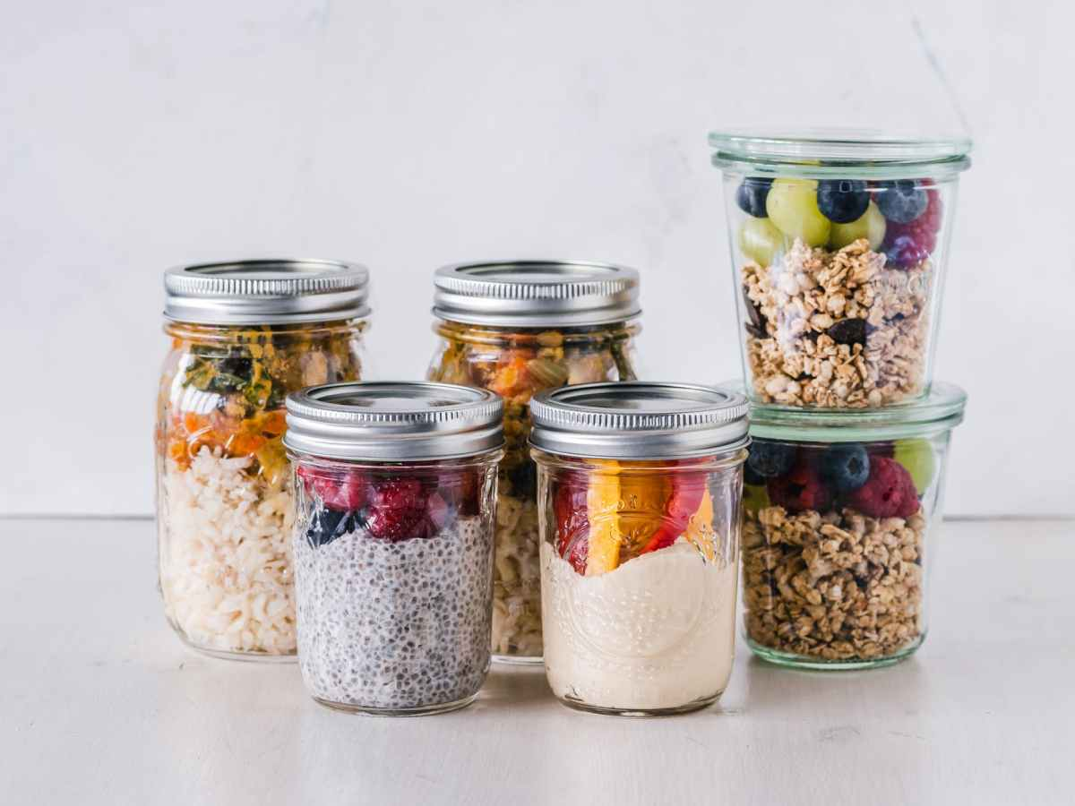 six fruit cereals in clear glass mason jars on white surface
