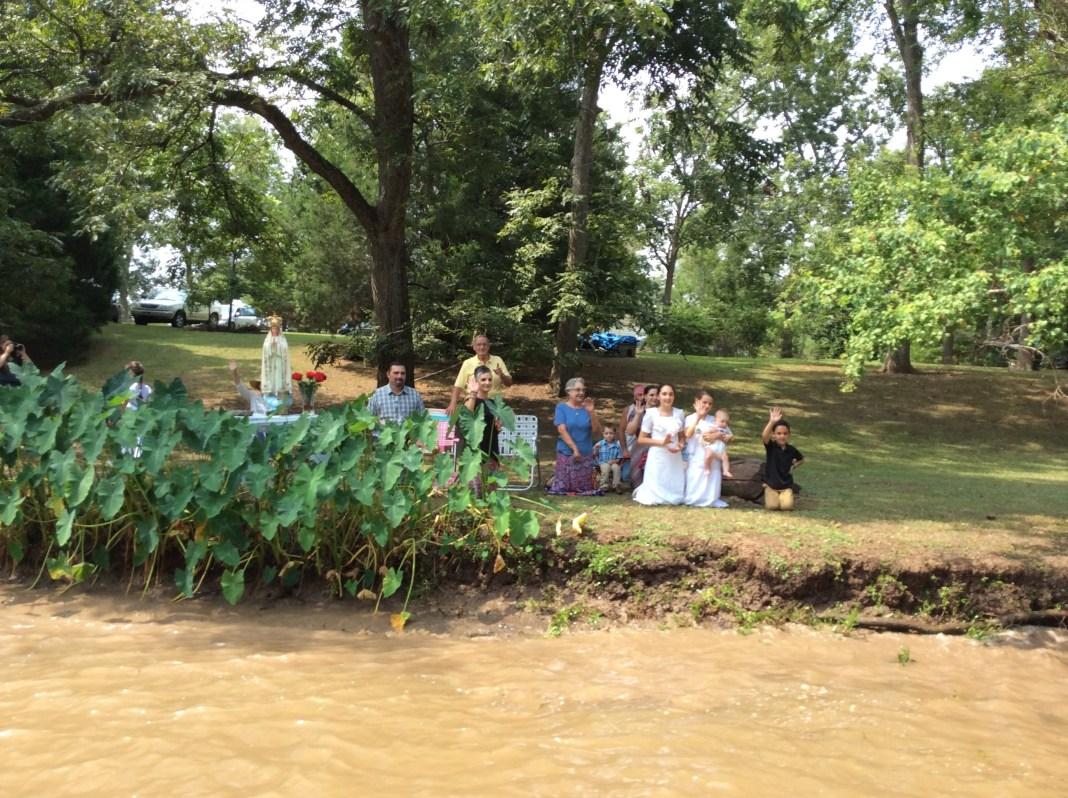 Familia de rodillas saludando el Santísimo y la Virgen  al costado del río