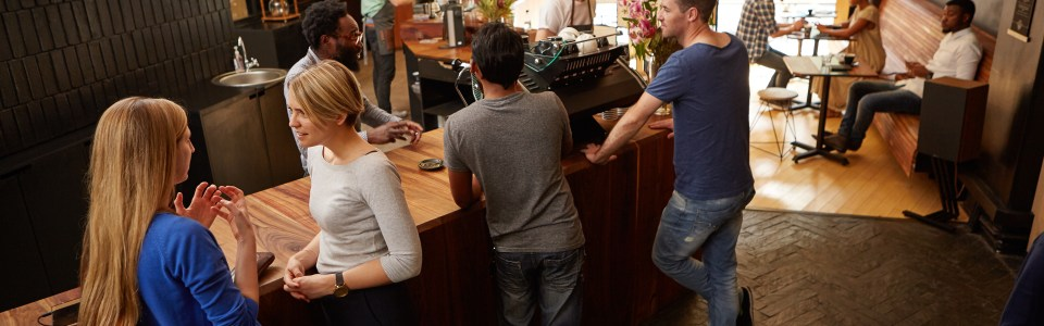 Women and men waiting at a modern coffee shop wooden counter talking and waiting for their coffee orders, while on their lunch break in a bright and stylish cafe