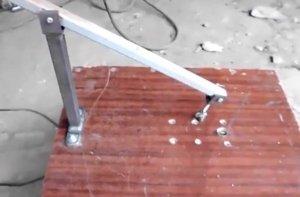 Tuas ketegangan ditetapkan pada permukaan kerja mesin pakan