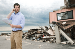 A man stands in front of a beach home that was destroyed by a hurricane