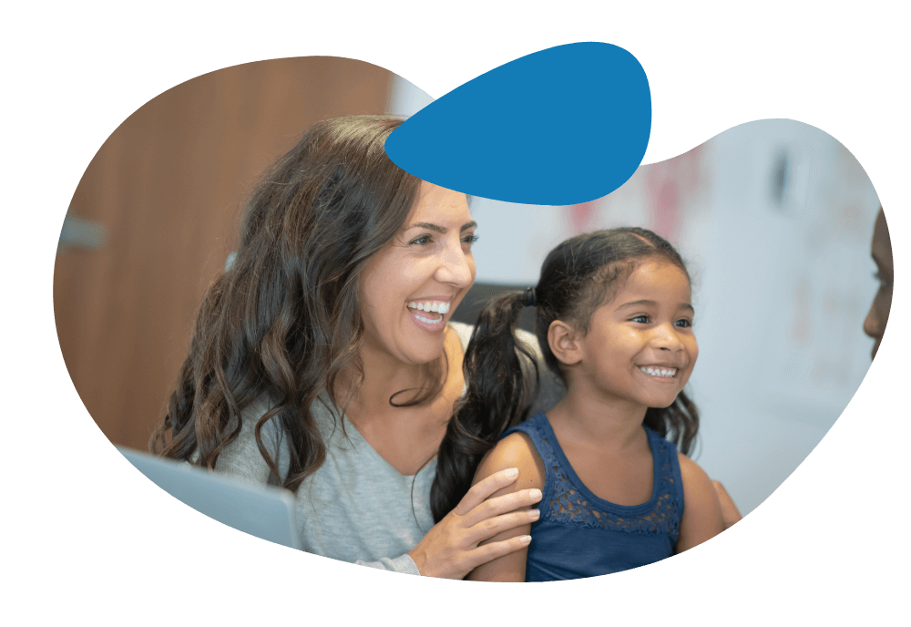 Woman smiling and laughing with her daughter while the doctor provides personalized, relationship driven care.