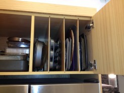 Over the refrigerator storage for baking sheets and casserole pans.
