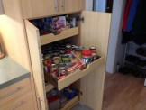 The original space of the refrigerator is now a little pantry with sliding shelves.