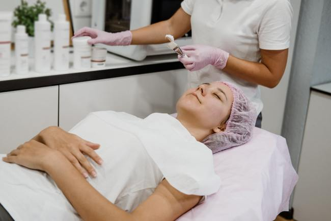 Professional Esthetician Apply Face Mask to the client's face in spa beauty center