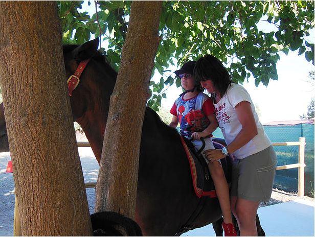 Monitora sosteniendo a niño sobre caballo