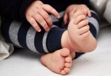 Bebé sentado, se destacan pies y manos