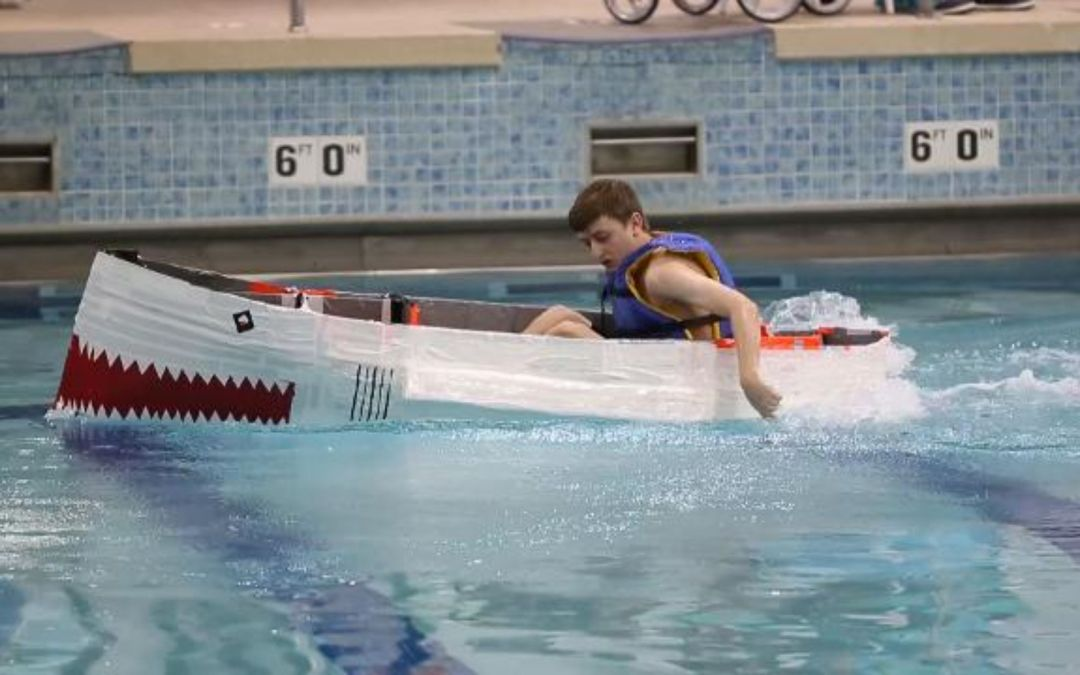 High school students race boats made of cardboard and duct tape