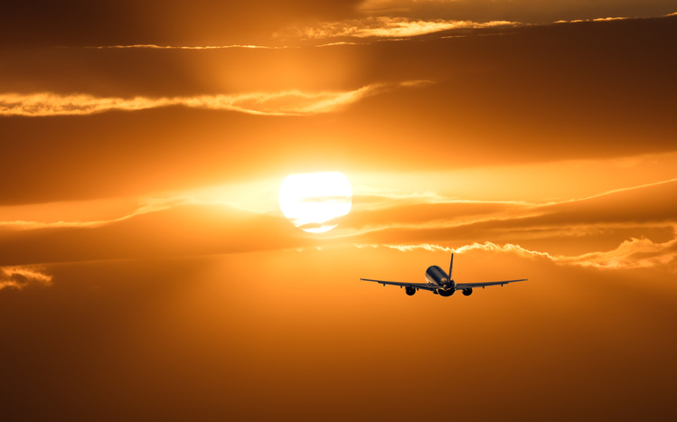 Plane in the distance flying towards a yellow sky and sunset