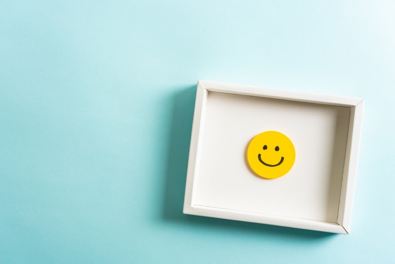 A smiley face in a small frame on a light blue background