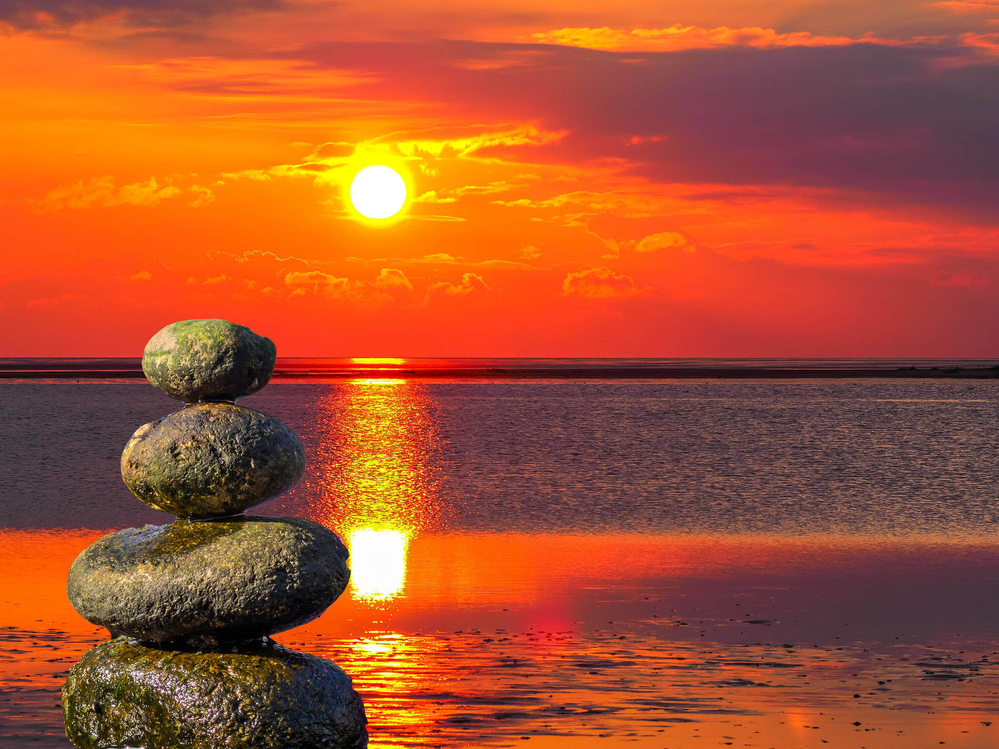 Balance stones at sunset with the sea in the background.