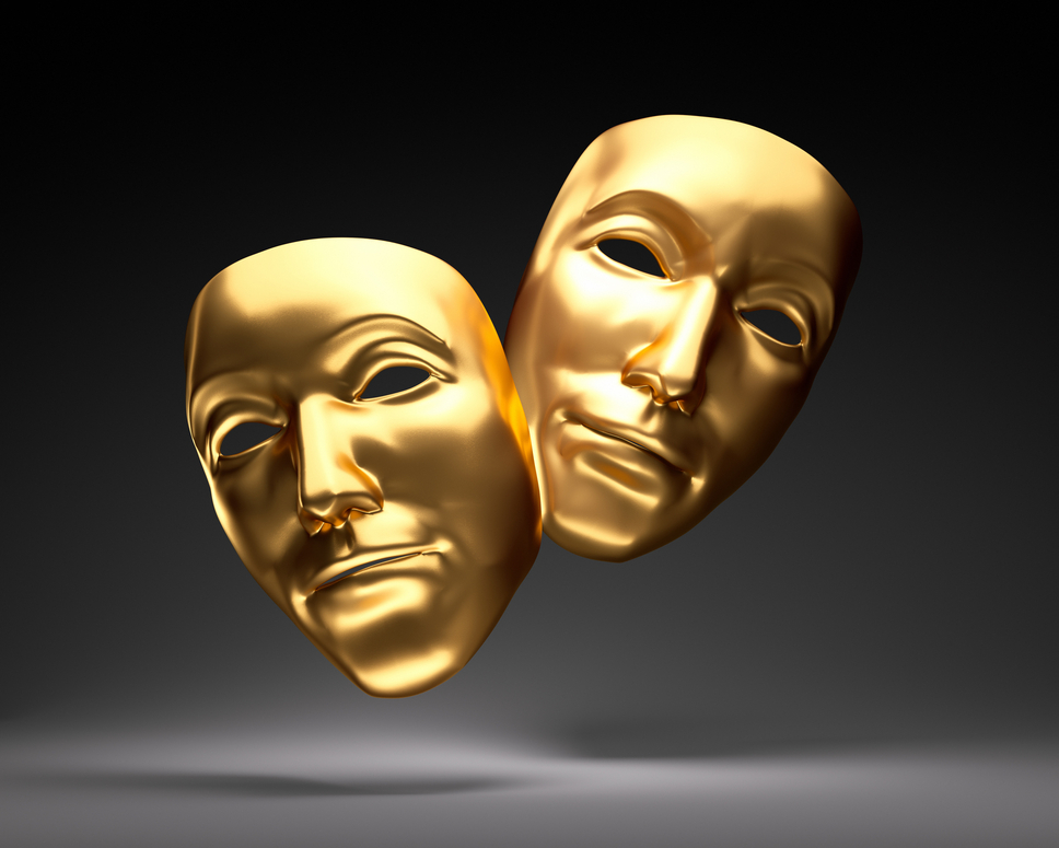 Two gold theater masks on a black shadowed background