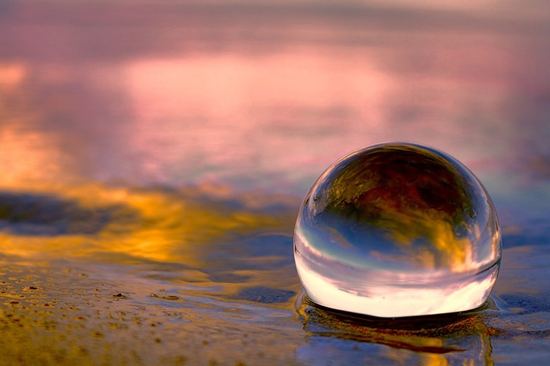 A glass globe resting on some sand and water with a background pink glow