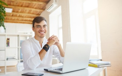 Portrait of happy successful young businessman wears white shirt and spectacles using laptop and cell phone sitting at the table in office and smiling