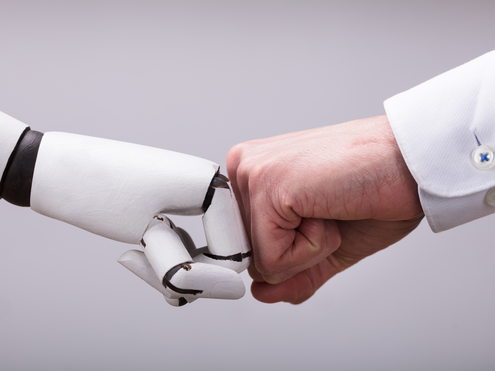 Roboter und Mensch geben sich einen Fist Bump
