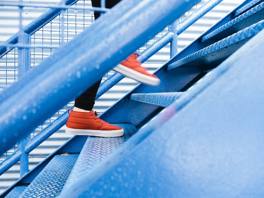 Leuchtend rote Schuhe steigen eine bläuliche Treppe hinauf. Sehr clean und kontrastreich.